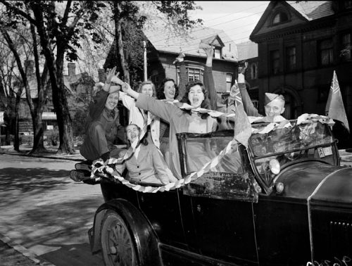 University students cheer in a car decorated with flags and streamers.