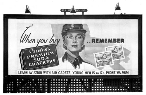 Billboard showing woman in armed forces uniform.