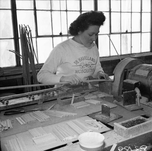A woman wearing a shirt that says De Havilland Mosquito works at a machine.