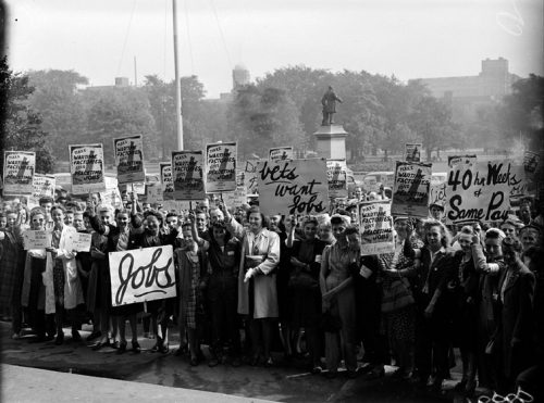 A large crowd holds up signs with slogans including 'Vets want jobs' and 'Make wartime factories give peacetime jobs' and '40 hour week & same pay.'