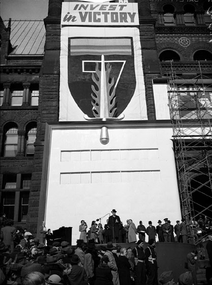 A huge banner is draped on the front of Old City Hall. It shows a shield with a flaming sword in it, and the words 'Invest in Victory.' On the ground, several people on a platform are watched by a crowd.
