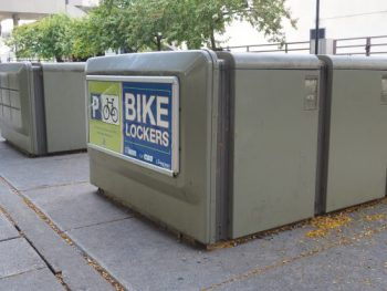Two rows of grey bicycle lockers at City Hall