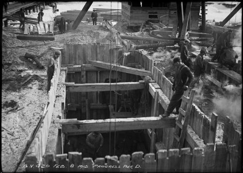 Workers in excavated pit lined with wooden supports.