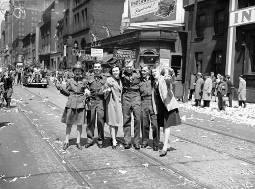 Six men and women, some in uniform, stand in a row, smiling and cheering at the camera. Some are waving flags. The street is covered in tickertape and other paper.