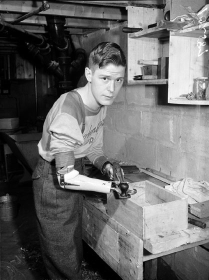 A young man with an artificial right arm and hand is planing a wooden box smooth.