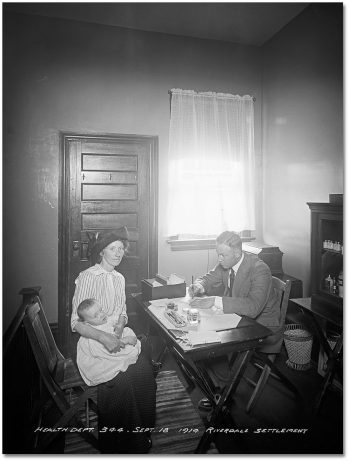 Sitting in front of a desk. a woman holds a baby on her lap, while the doctor on the other side of the desk looks at the baby and writes something on a piece of paper.