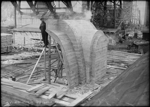 Man standing beside arch-shaped wooden mould twice as tall as he is.