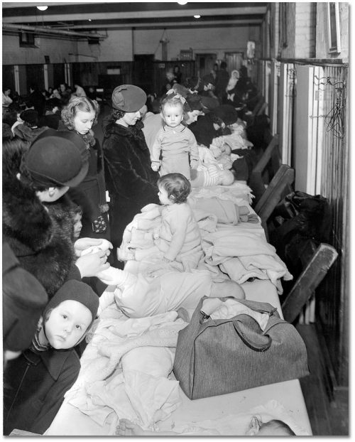 Mothers in winter coats dress babies on a long table covering in clothing.