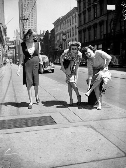 Two women standing on a sidewalk bend over to hold their feet and legs, and make faces to show how much their feet hurt. Another woman laughs as she walks past them.