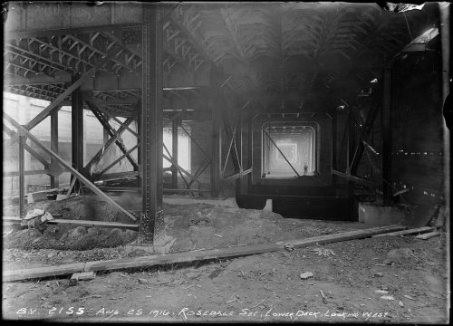 Underneath bridge with riveted metal supports holding it up.