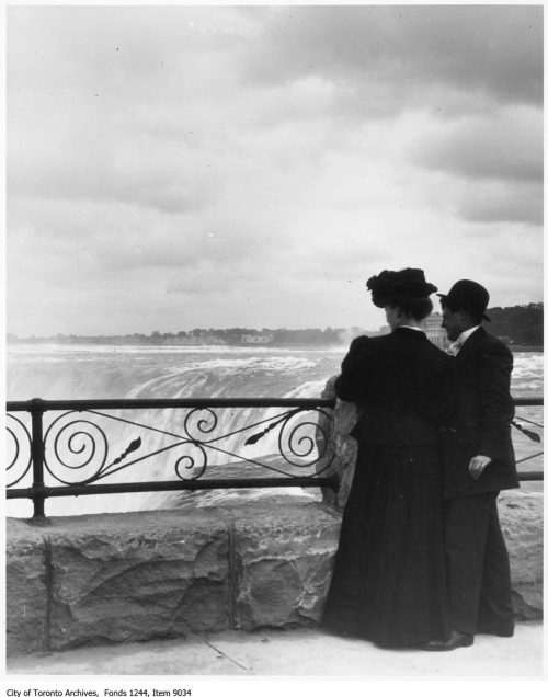 Two people look over a wrought iron fence to Niagara Falls.
