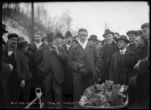 Men in suits and coats surrounding a wheelbarrow full of clods of earth.