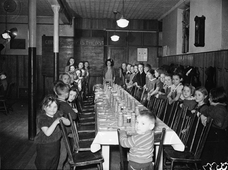 Children standing behind chairs at a long dinner table.