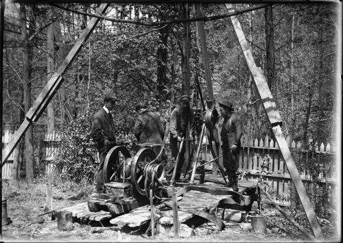 Men operating a machine with wheels under a large wooden tripod.