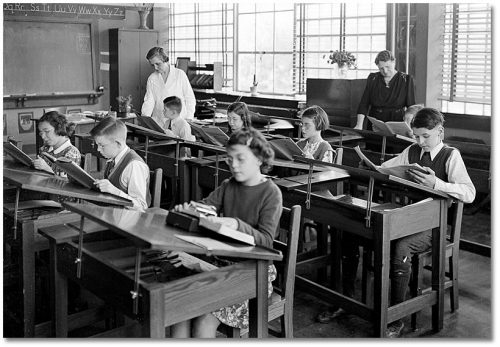 Children read books in a classroom with large windows and slanting desktops. Some are wearing glasses.