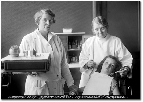 Two women who are dentists stand over a girl in a dentist's chair.