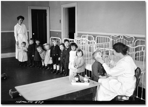 Nurse looking into a child's mouth while a line of children looks on.
