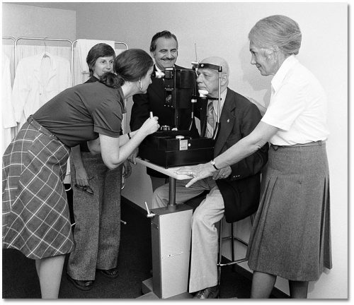 An optometrist examines an elderly man's eyes using a machine while other people watch.