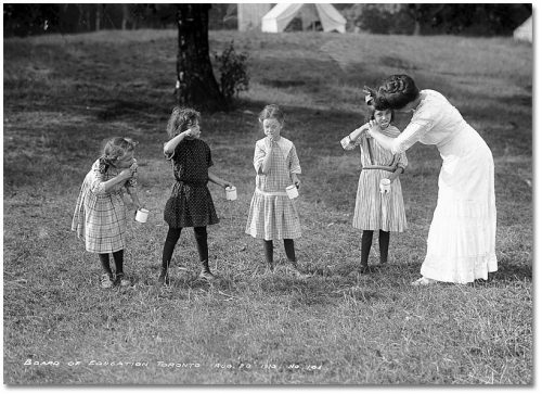 Four girls stand on the grass with mugs in their hands, brushing their teeth, while a teacher helps one of them.