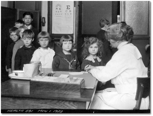 Children line up in front of a nurse at a desk.