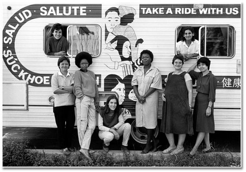 Women of colour and of different ethnicities stand in front of a trailer that is painted with Hello in various languages.