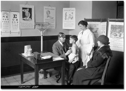 A doctor listens to a boy's chest with a stethoscope in a corner of a room with illustrated posters about healthy habits all over the walls.