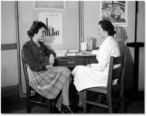 A nurse in a white lab coat and a teenage girl wearing a plaid skirt talk at a desk while the nurse takes notes.