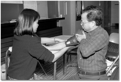 A woman tests a man's blood pressure using a cuff.