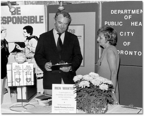 A man and woman stand in a booth that displays informational posters and brochures about birth control.