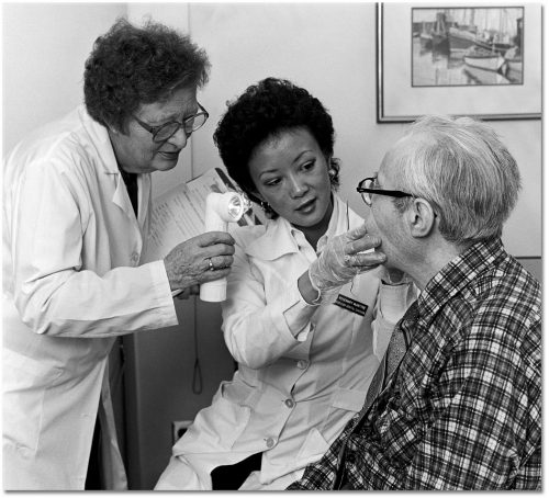 Two dentists in white lab coats examine an elderly man's teeth.