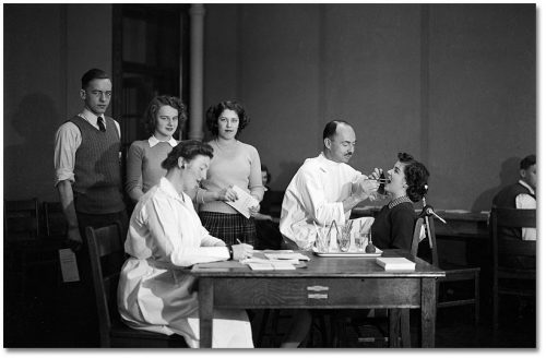 A dentist looks in a teenage girl's mouth, while a line of teenagers stands beside a woman in a lab coat taking notes at a desk.