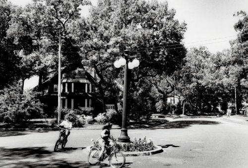 This is an archival photograph of two children on bikes circling a lamppost in Baby Point, taken in 1985