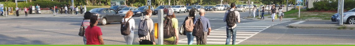 A group of youths with backpacks cross a busy street at a crosswalk