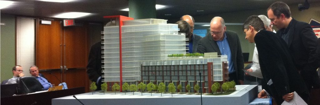 Photo of design review panel members looking at building model