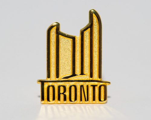 Picture of a City of Toronto Lapel pin featuring two towers and the City Toronto logo