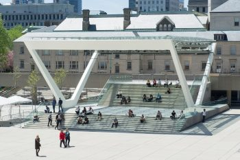 View of the theatre stage in Nathan Phillips Square, where people can be seen sitting on the steps eating their lunch and enjoying the sunny weather
