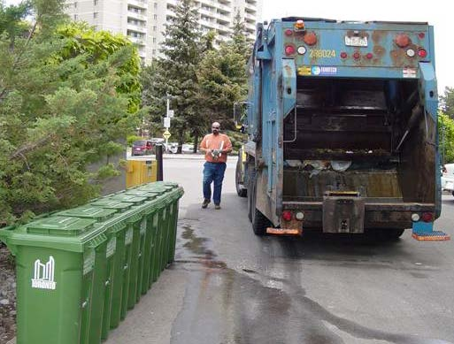 Collection truck and worker in front of a row of new Green Bins