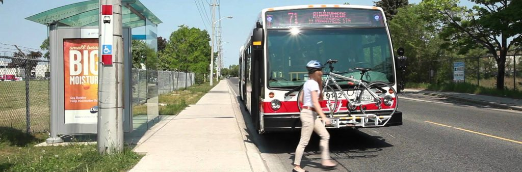Image of a stopped TTC Bus. A women is hooking up her bike to the front of the bus.