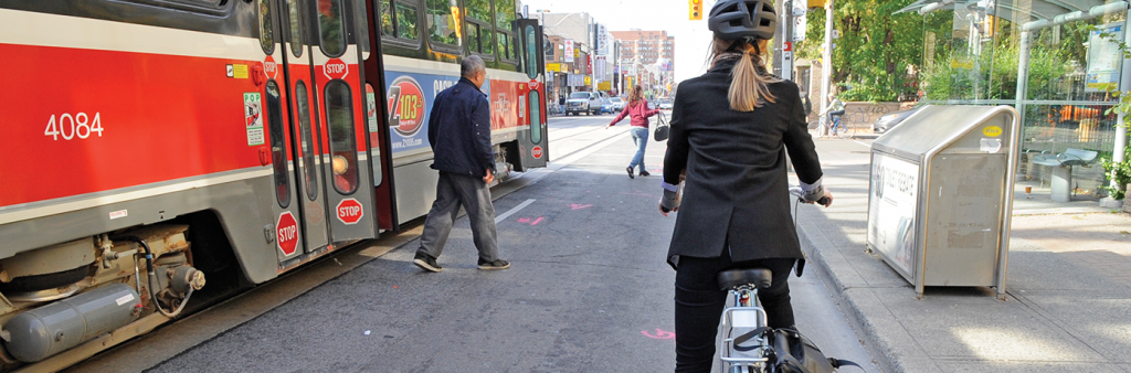 Image of Cyclist waiting for pedestrians to get on and off the TTC streetcar