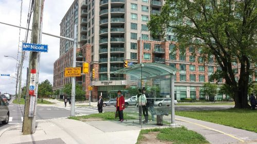 Image of green space, sidewalk, bike lanes and accessible covered bus stop in Scarborough