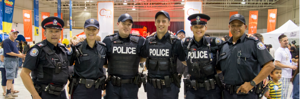 Uniformed officers standing arm in arm smiling at camera
