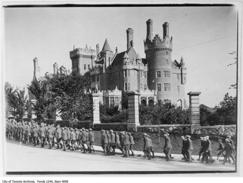 This is an archival photograph of soldiers marching on Walmer Road in front of Casa Loma in 1914.