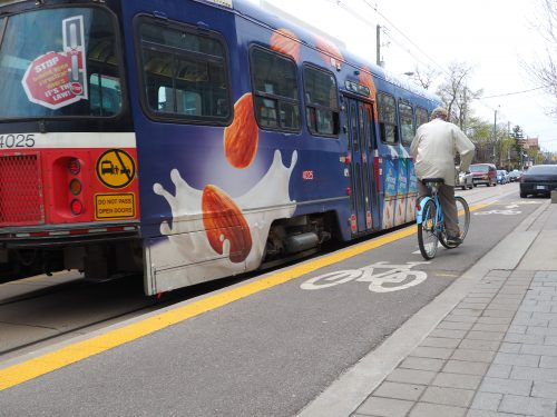 Cyclists waits 2 meters behind the streetcar doors before continuing forward