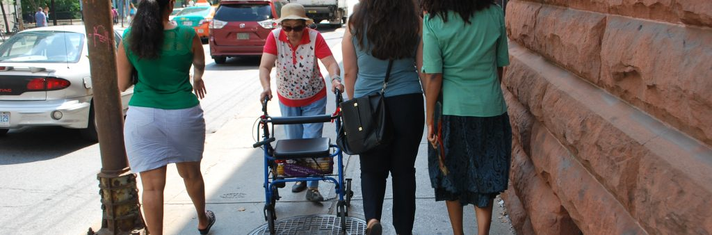 Image of an older lady walking on the sidewalk with a walker