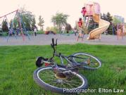 A child leaves their bicycle on the ground and goes to play on a slide at a playground.