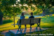 In Riverdale Park, two people sitting on a bench taking in the view of the sunlight.