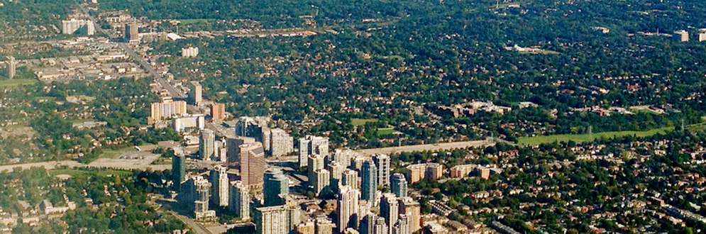 An aerial image of high rise buildings surrounded by low rise neighbourhoods and trees