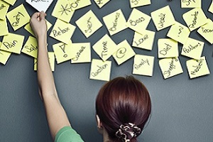 Lady Adding Post-It Note to Wall