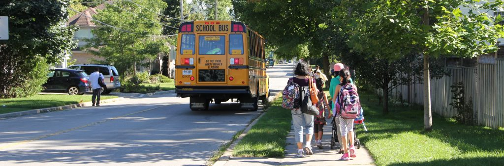 School bus with children walking on the sidewalk