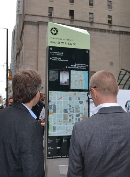 People interacting with the TO360 sign.